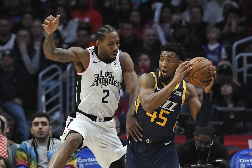Los Angeles Clippers forward Kawhi Leonard, left, defends against Utah Jazz guard Donovan Mitchell during the second half of an NBA basketball game Sa...