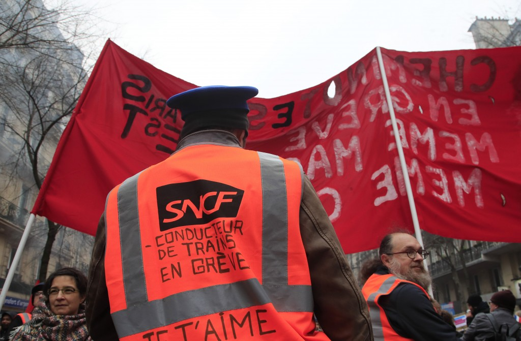 "A rail worker wears a jacket with the inscription, "" train driver on strike""during a protest against pension reform plans in Paris, Saturday, Dec. 28,..."
