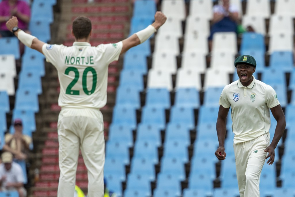 South Africa's Kagiso Rabada, right, celebrates with teammate bowler Anrich Nortje after taking a catch to dismiss England's batsman Rory Burns for 84...