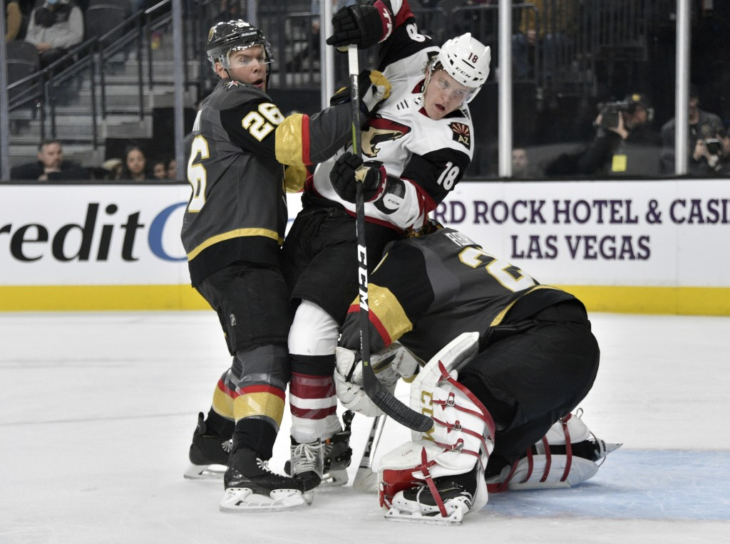 Arizona Coyotes center Christian Dvorak (18) is sandwiched between center Vegas Golden Knights Paul Stastny (26) and goaltender Marc-Andre Fleury (29)...