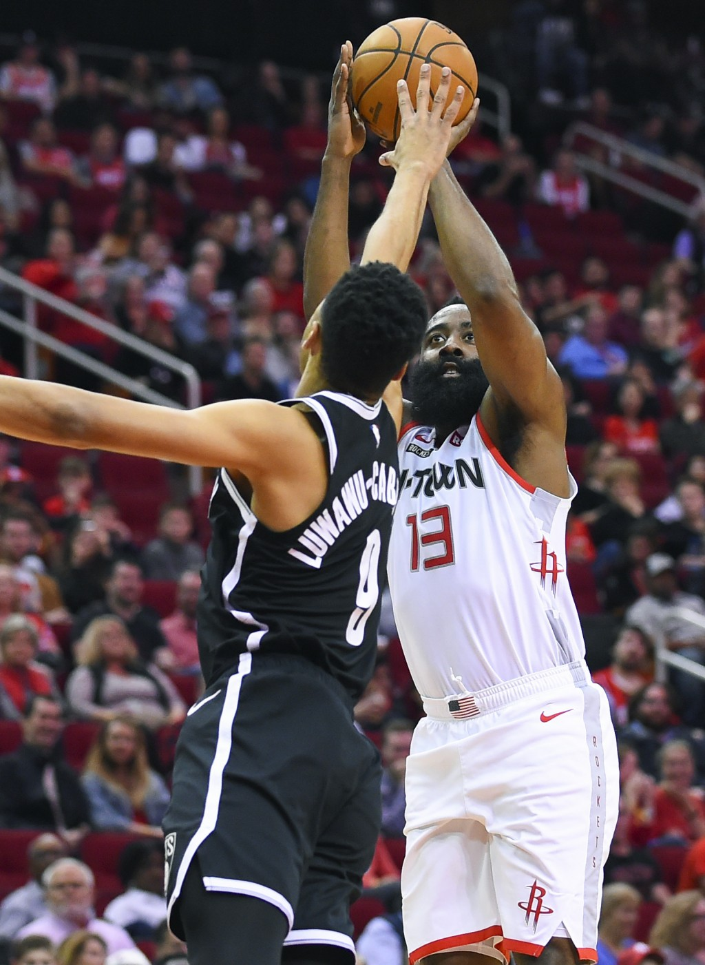 Houston Rockets guard James Harden, right, shoots as Brooklyn Nets guard Timothe Luwawu-Cabarrot defends during the first half of an NBA basketball ga...