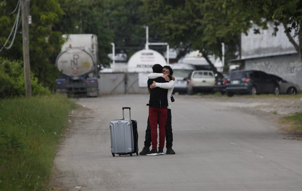 A man who was deported from the United States, foreground, is welcomed by a relative outside the Ramon Villeda International Airport in La Lima, Hondu...