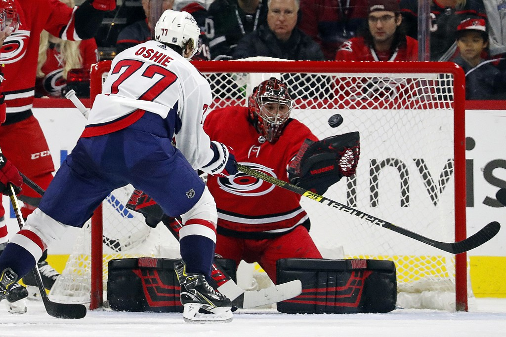 Carolina Hurricanes goaltender Petr Mrazek, right, of the Czech Republic, watches the puck in front of Washington Capitals' T.J. Oshie (77) during the...