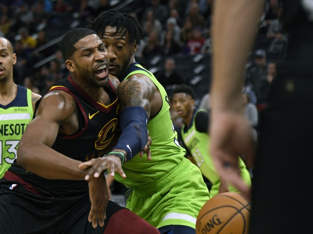 Minnesota Timberwolves' Robert Covington, right, knocks the ball away from Cleveland Cavaliers' Tristan Thompson during the first quarter of an NBA ba...