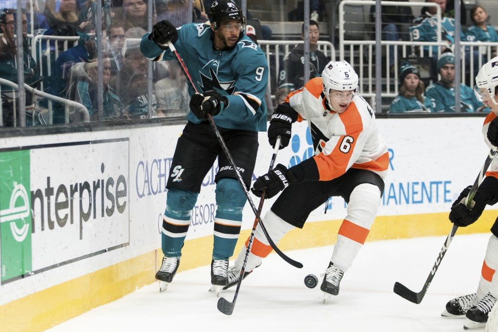 San Jose Sharks left wing Evander Kane (9) and Philadelphia Flyers defenseman Travis Sanheim (6) compete for possession of the puck during the first p...