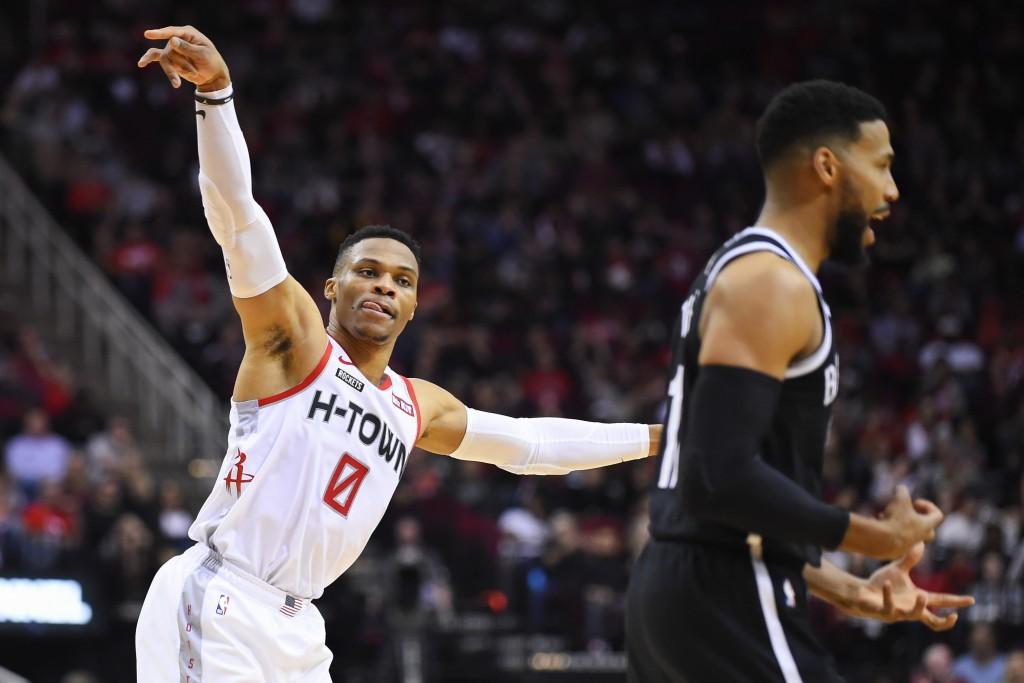 Houston Rockets guard Russell Westbrook (0) gestures toward Brooklyn Nets guard Garrett Temple after making a basket during the first half of an NBA b...