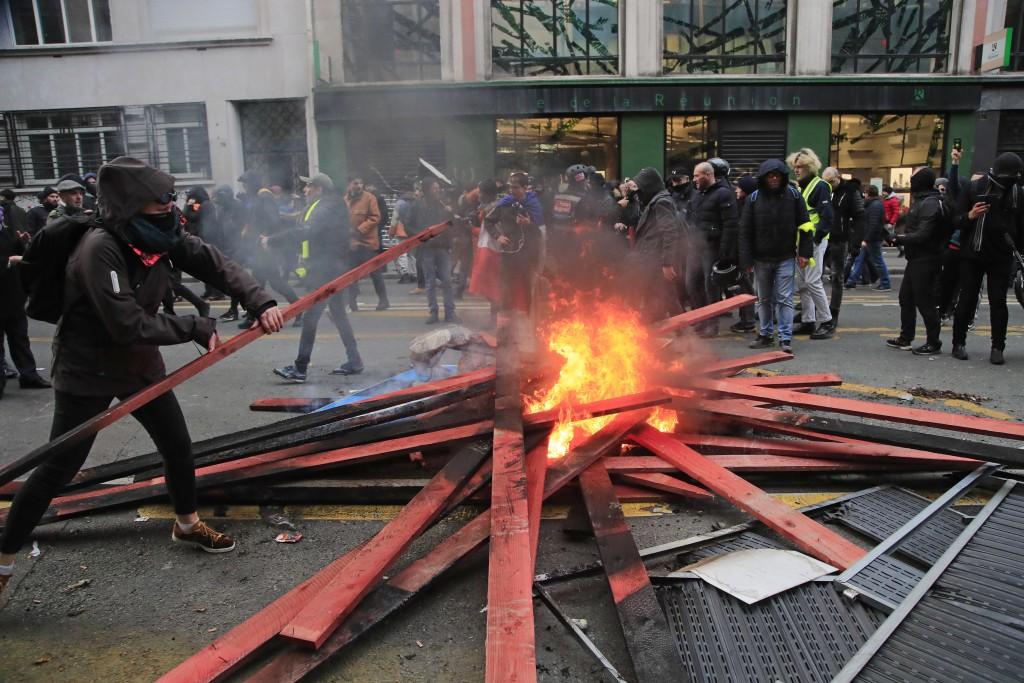 A demonstrators set up a barricade and light fire during a protest against pension reform plans in Paris, Saturday, Dec. 28, 2019. Thousands of protes...