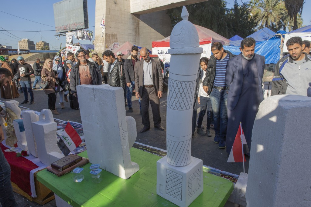 In this Friday, Dec. 20, 2019, photo, protesters attend the opening of an art exhibition in Tahrir square, Baghdad, Iraq. Tahrir Square has emerged as...