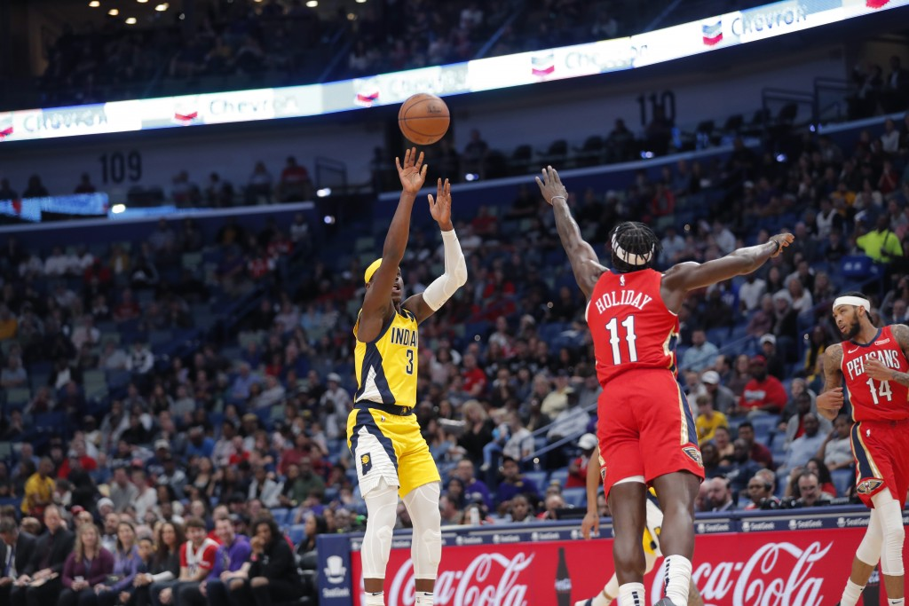 Indiana Pacers guard Aaron Holiday (3) shoots a 3-pointer over his brother, New Orleans Pelicans guard Jrue Holiday (11), during the first half of an ...