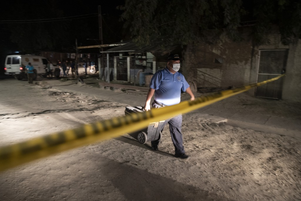 A forensic worker leaves a crime scene after inspecting the body of a man fatally shot in the streets of the Rivera Hernandez neighborhood in San Pedr...