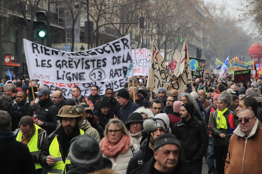 Demonstrators march with banners during a protest against pension reform plans in Paris, Saturday, Dec. 28, 2019. Thousands of protesters opposed to t...