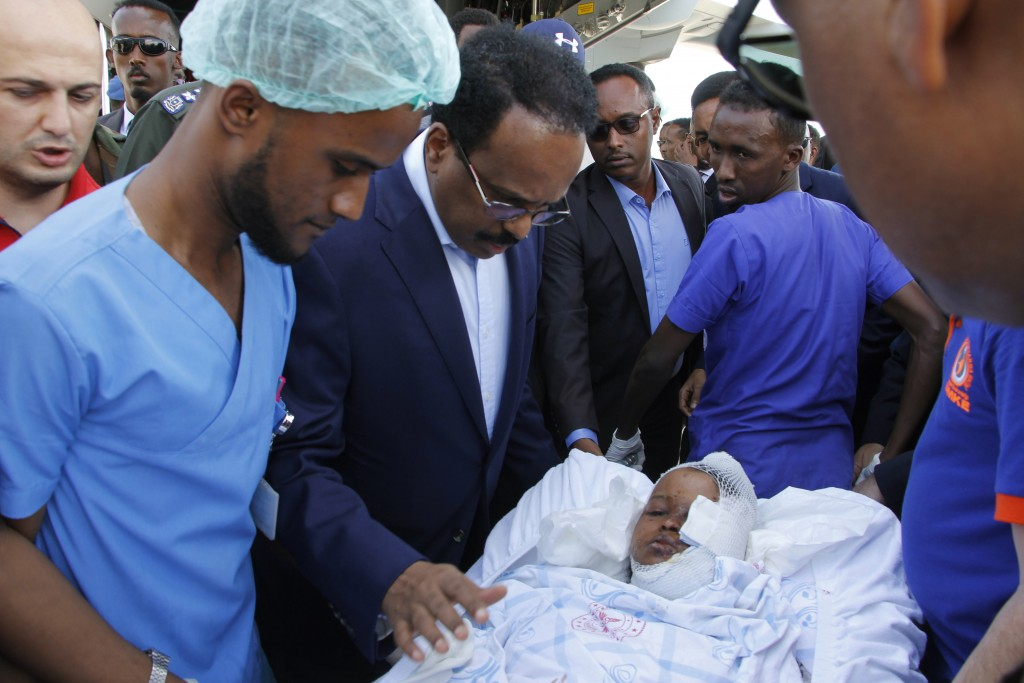 Somalia's President Mohamed Abdullahi Mohamed reacts with a wounded person to be airlifted to the Turkish capital for treatment after being injured in...