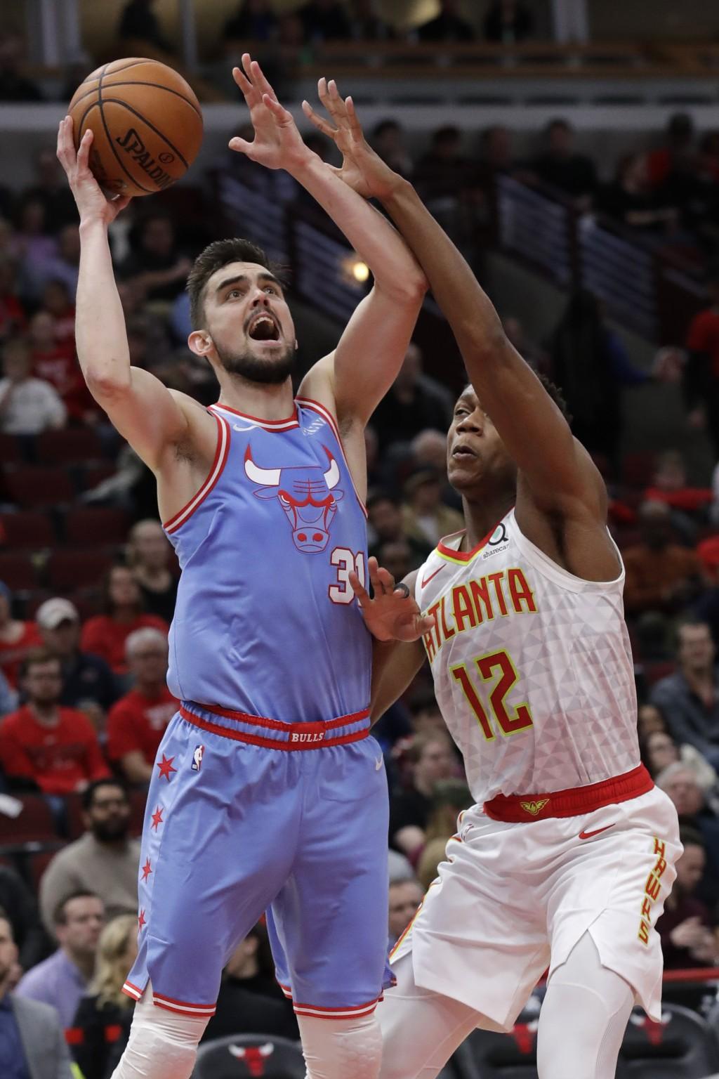 Chicago Bulls guard Tomas Satoransky, left, shoots against Atlanta Hawks forward De'Andre Hunter during the second half of an NBA basketball game Satu...