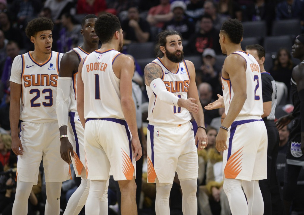 Phoenix Suns guard Ricky Rubio, second from right, talks with teammate Elie Okobo, right, during the first quarter of an NBA basketball game against t...
