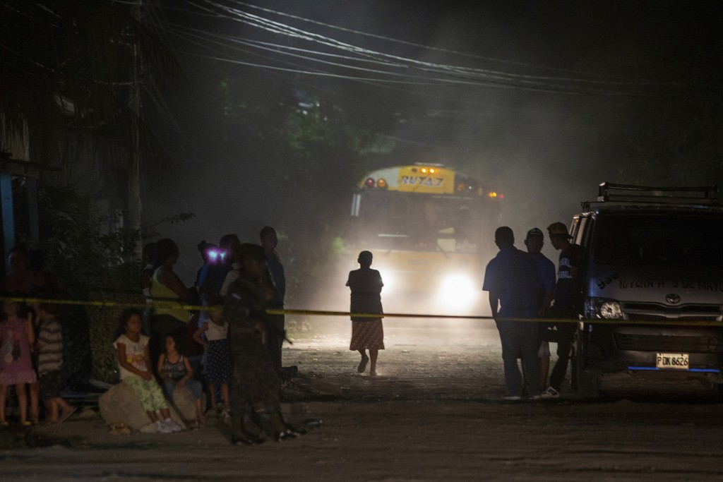 Neighbors watch as police and forensic workers inspect a body at a crime scene in the Rivera Hernandez neighborhood of San Pedro Sula, Honduras, on No...