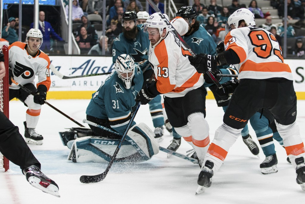 Philadelphia Flyers center Kevin Hayes (13) collides with San Jose Sharks goaltender Martin Jones (31) during the second period of an NHL hockey game ...