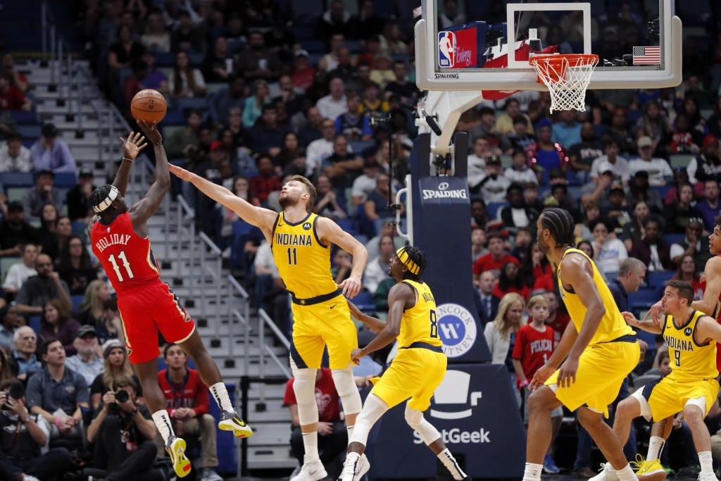 New Orleans Pelicans guard Jrue Holiday (11) shoots against Indiana Pacers forward Domantas Sabonis (11) during the first half of an NBA basketball ga...