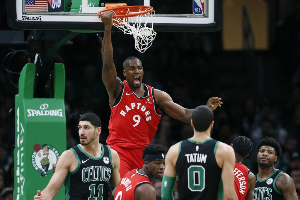Toronto Raptors' Serge Ibaka (9) reacts after his dunk during the first half on an NBA basketball game against the Boston Celtics in Boston, Saturday,...