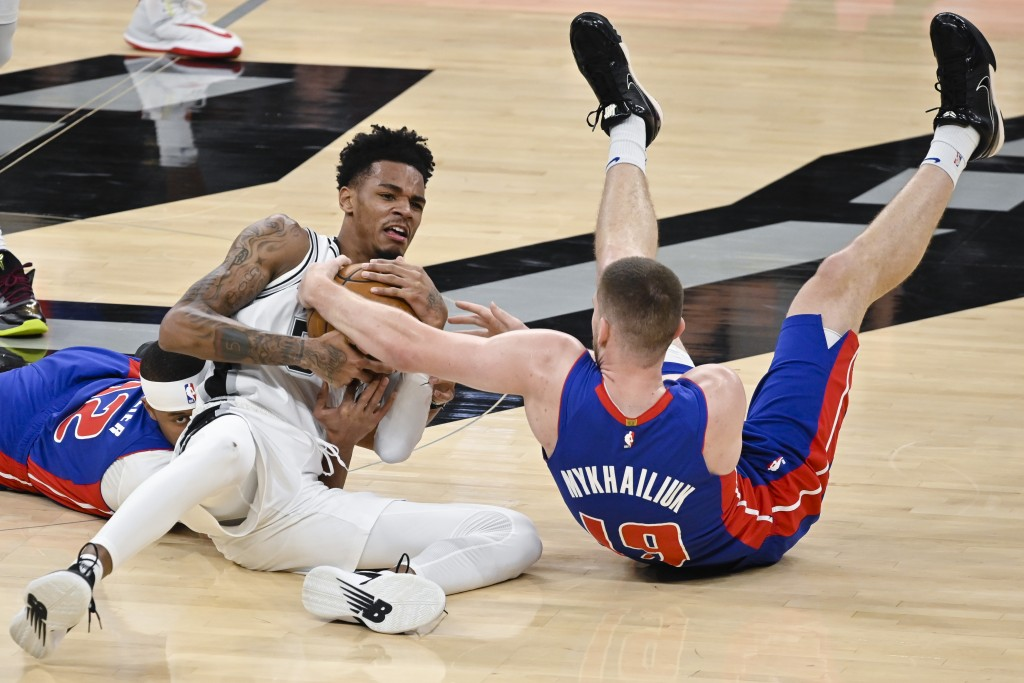 San Antonio Spurs guard Dejounte Murray, center, fights for possession with Detroit Pistons' Svi Mykhailiuk, right, and Tim Frazier during the second ...