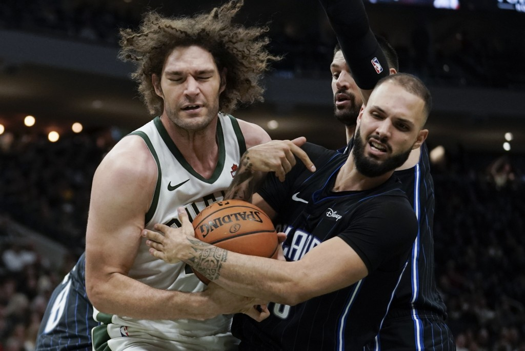 Milwaukee Bucks' Robin Lopez and Orlando Magic's Evan Fournier battle for a rebound during the second half of an NBA basketball game Saturday, Dec. 28...