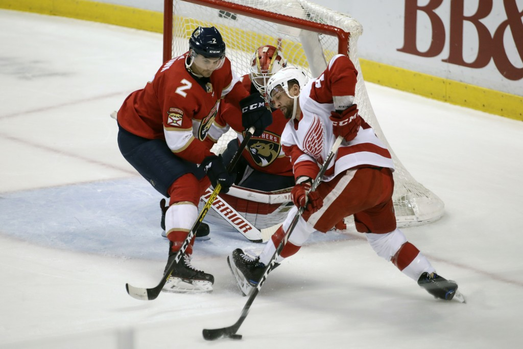 Detroit Red Wings' Luke Glendening, right, moves the puck as Florida Panthers' Josh Brown (2) and goalkeeper Chris Driedger defend during the first pe...