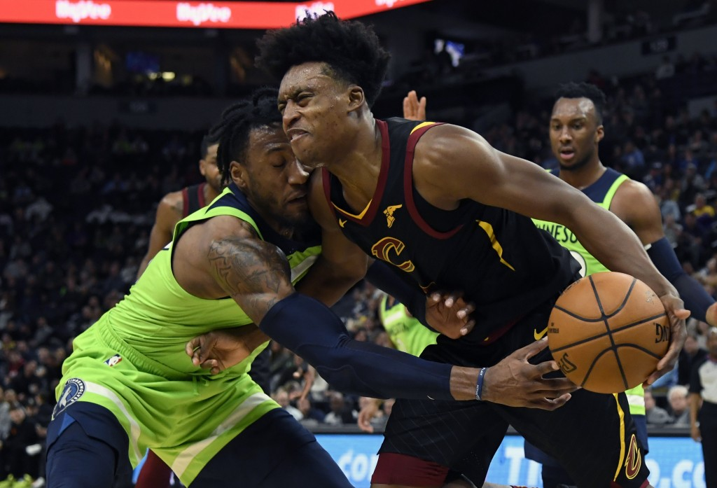 Minnesota Timberwolves' Robert Covington (33) reaches for the ball controlled by Cleveland Cavaliers' Collin Sexton (2) during the second quarter of a...