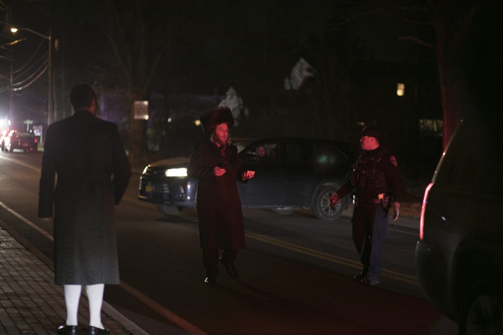An officer asks an Orthodox Jewish man to stay off the car lane as authorities gather on the street in Monsey, N.Y., Sunday, Dec. 29, 2019, following ...