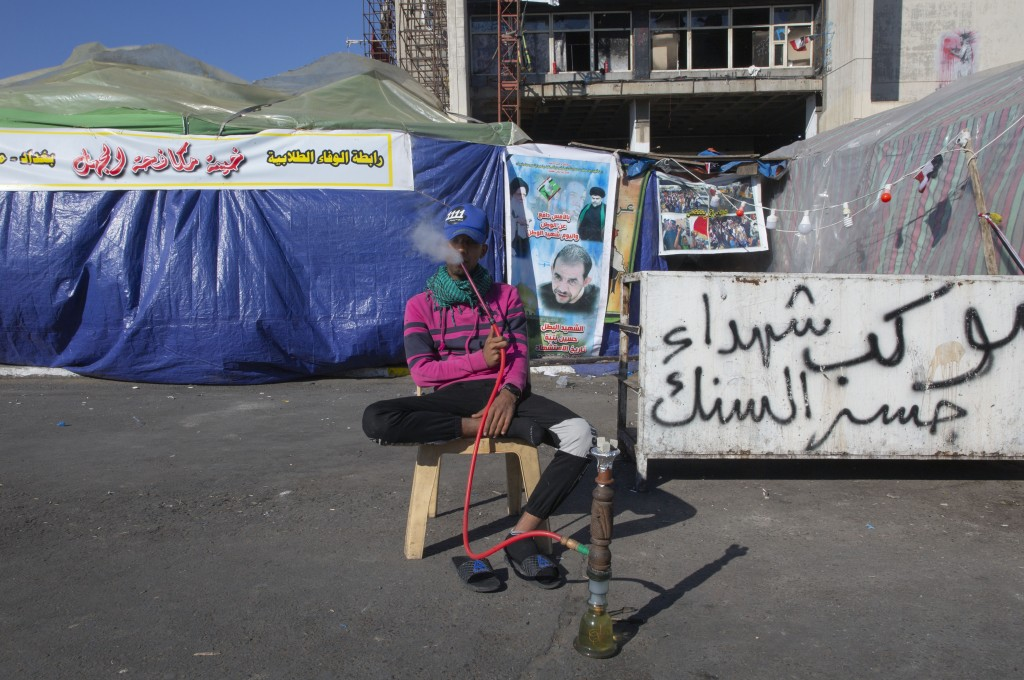 """In this Thursday, Dec. 19, 2019, photo, a youth protester rests and smokes a water pipe next to Arabic that reads """"the convoy of the Al-Sanak bridge M..."""