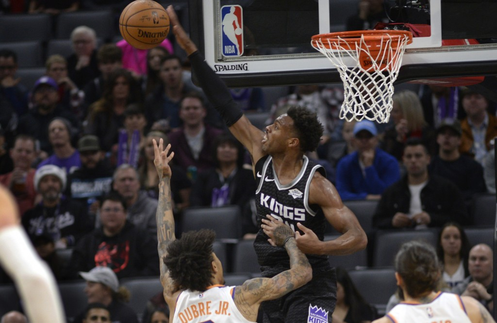 Sacramento Kings guard Buddy Hield, right, blocks a shot by Phoenix Suns forward Kelly Oubre Jr., left, during the first quarter of an NBA basketball ...