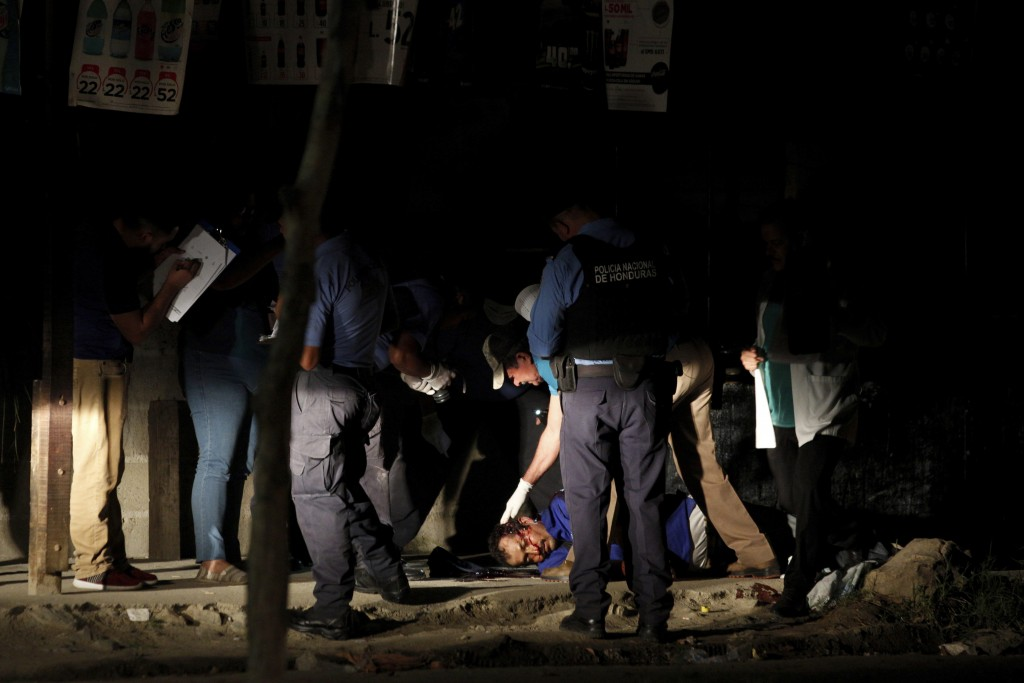 The body of a man lies in the middle of a street as police and forensic workers inspect the crime scene in the Rivera Hernandez neighborhood of San Pe...