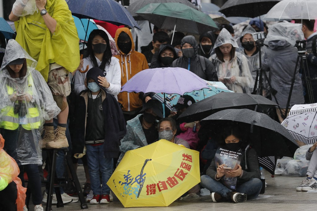 """Protesters sit down near an umbrella with the words """"Support freedom, Against Evil Law"""" during a rally in Hong Kong on Sunday, Dec. 29, 2019. Protests..."""