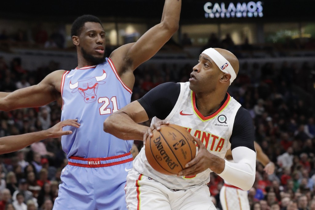 Atlanta Hawks guard/forward Vince Carter, right, looks to pass as Chicago Bulls forward Thaddeus Young guards during the first half of an NBA basketba...