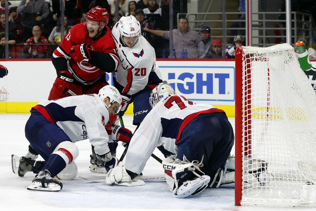 Carolina Hurricanes' Warren Foegele (13) reacts after finding the puck and getting it past Washington Capitals goaltender Braden Holtby (70), of Switz...