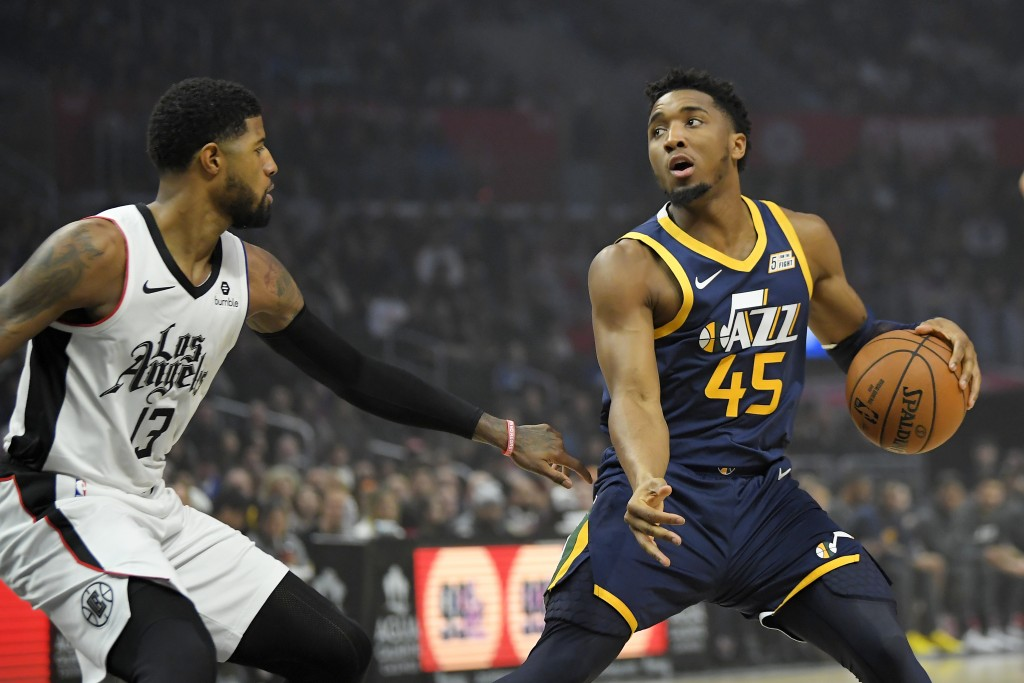 Utah Jazz guard Donovan Mitchell, right, tries to drive by Los Angeles Clippers forward Paul George during the first half of an NBA basketball game Sa...