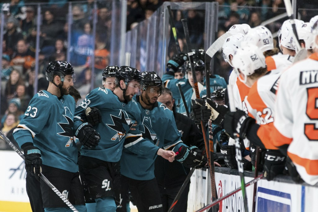 San Jose Sharks center Melker Karlsson (68) is helped off the ice by Barclay Goodrow (23) and other players after being hit by a shot by the Philadelp...