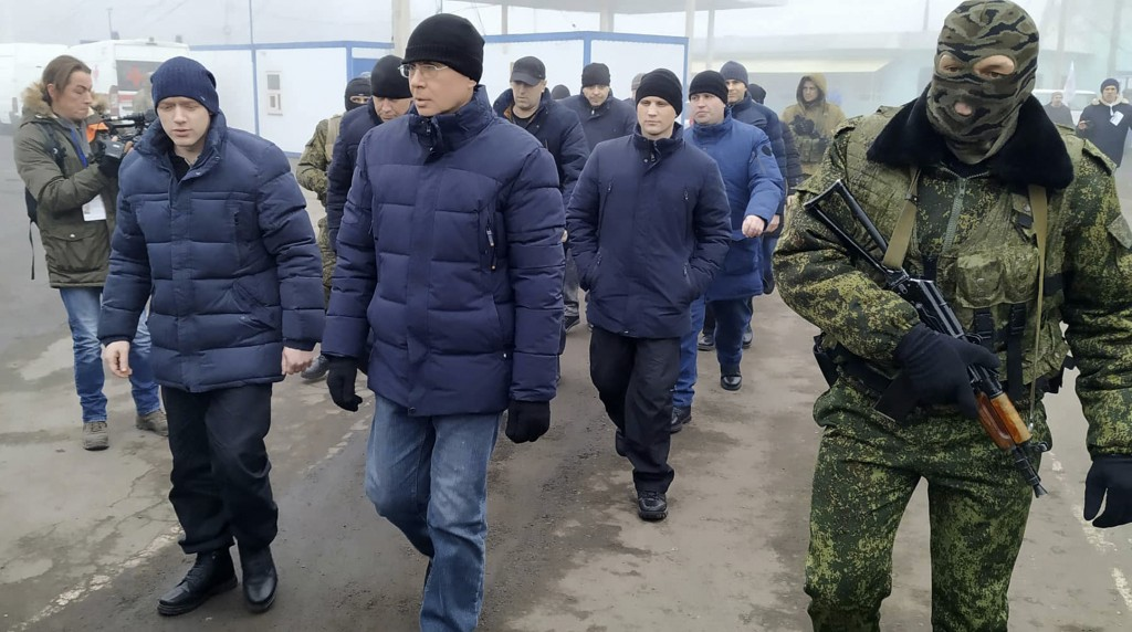 A Russia-backed separatist soldier escorts a group of separatists war prisoners after they were exchanged near the checkpoint Horlivka, eastern Ukrain...