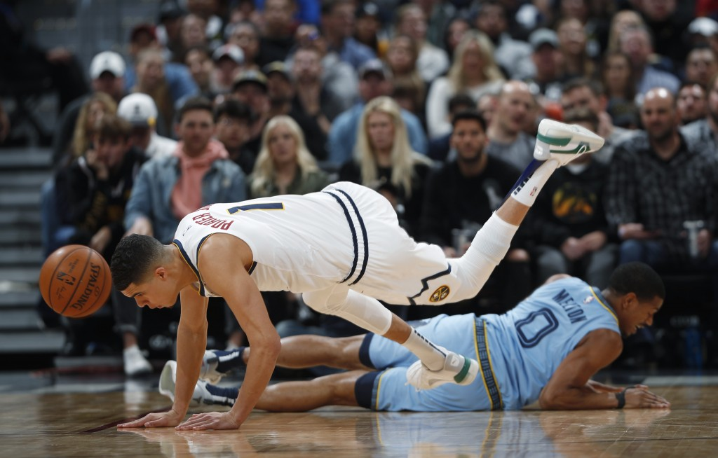 Denver Nuggets forward Michael Porter Jr., front, loses control of the ball and his footing after colliding with Memphis Grizzlies guard De'Anthony Me...