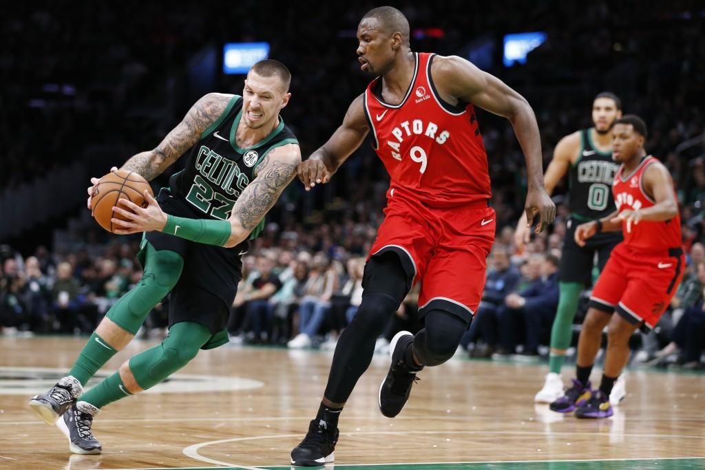 Toronto Raptors' Serge Ibaka (9) defends against Boston Celtics' Daniel Theis (27) during the first half on an NBA basketball game in Boston, Saturday...