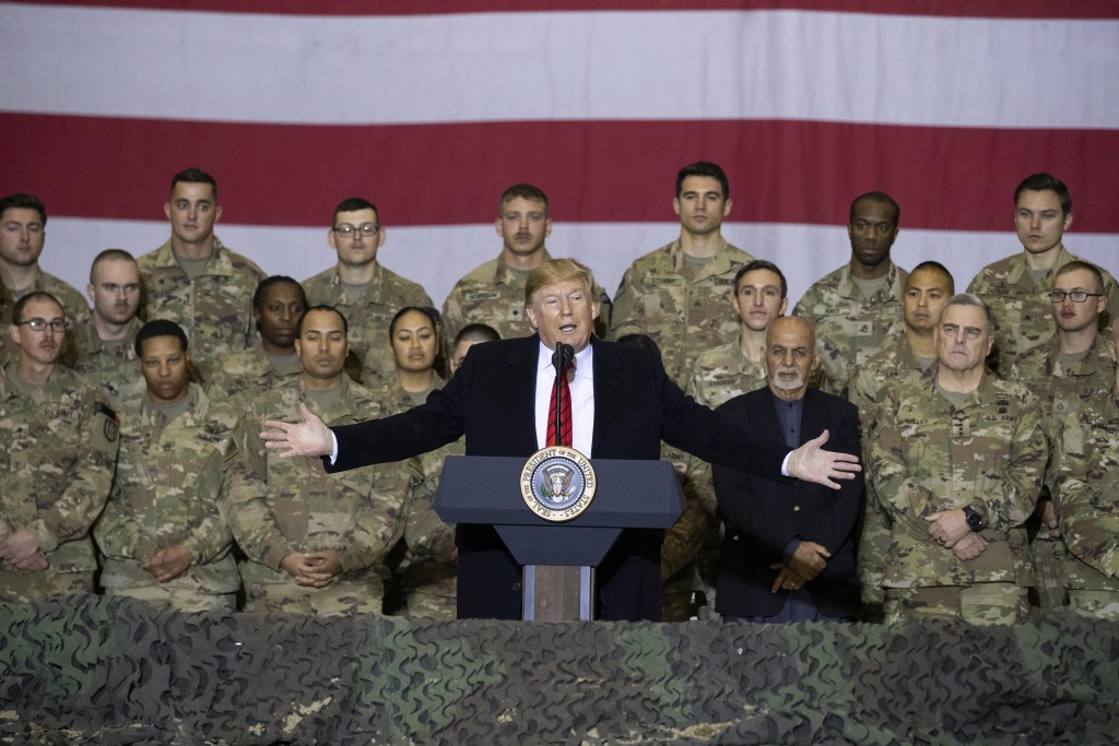 FILE - In this Nov. 28, 2019 file photo, President Donald Trump, center, with Afghan President Ashraf Ghani and Joint Chiefs Chairman Gen. Mark Milley...