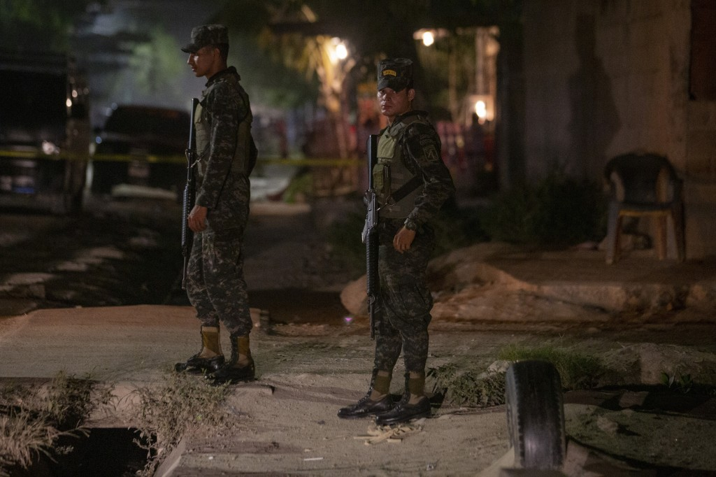 In this Nov. 30, 2019 photo, soldiers stand guard near a crime scene as forensic workers inspect a body in the Rivera Hernandez neighborhood of San Pe...