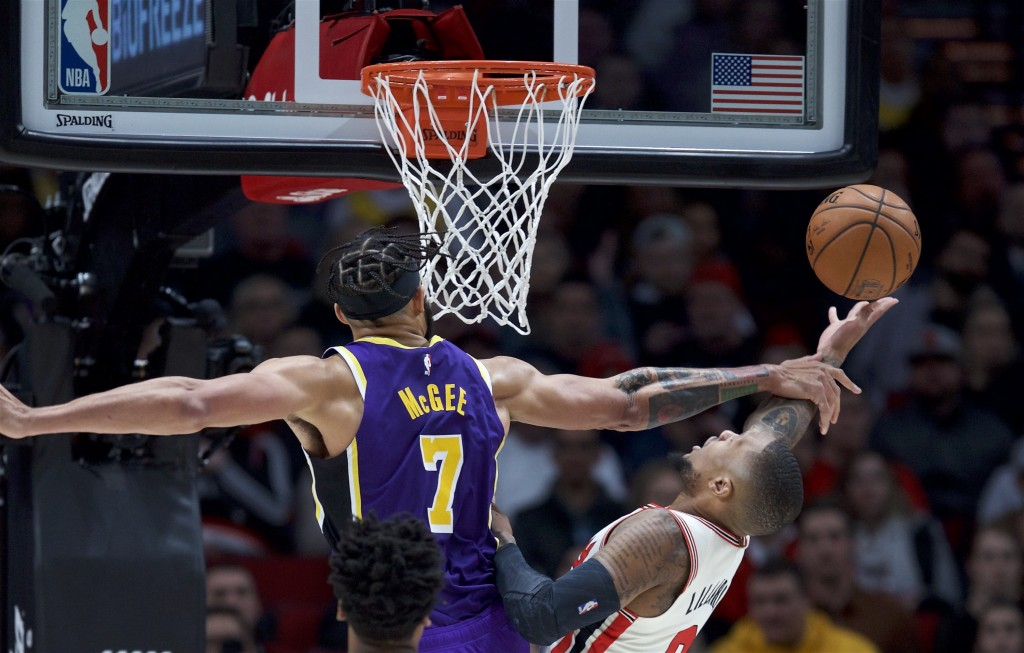 Portland Trail Blazers guard Damian Lillard, right, is fouled by Los Angeles Lakers center JaVale McGee during the first half of an NBA basketball gam...