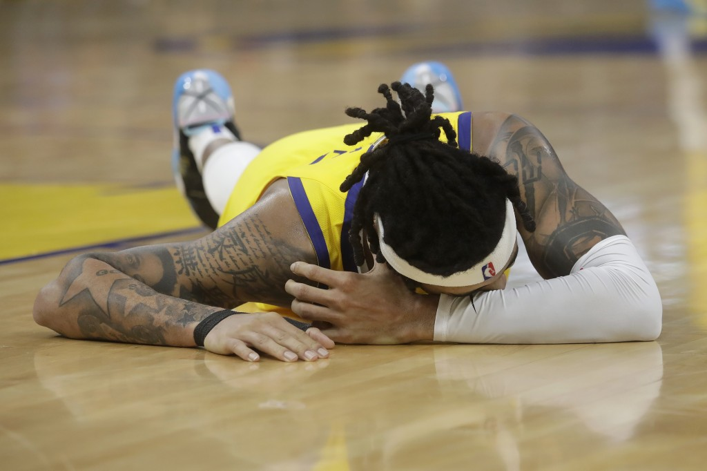 Golden State Warriors guard D'Angelo Russell remains on the floor after being injured during the second half of an NBA basketball game against the Dal...