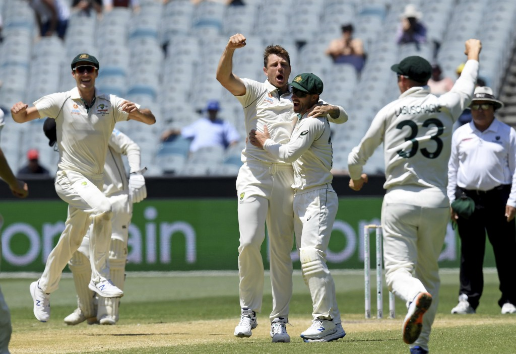 Australia's James Pattinson, center, celebrates with teammates after capturing the wicket of New Zealand's Kane Williamson during their cricket test m...