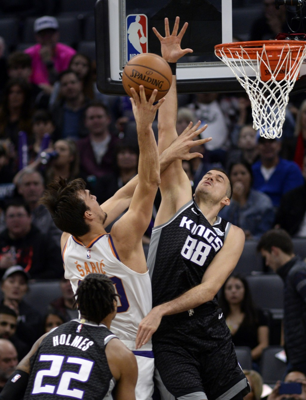 Phoenix Suns forward Dario Saric, center, goes to the basket against Sacramento Kings forward Nemanja Bjelica, right, during the first quarter of an N...