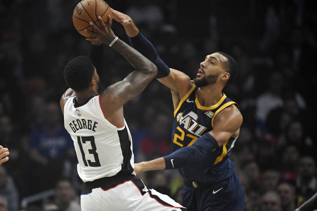Los Angeles Clippers forward Paul George, left, shoots as Utah Jazz center Rudy Gobert defends during the first half of an NBA basketball game Saturda...