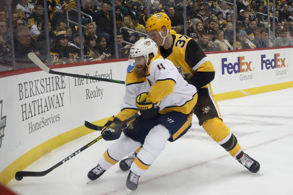 Nashville Predators' Ryan Ellis (4) goes into the corner for the puck as Pittsburgh Penguins' Sam Lafferty (37) pursues during the second period of an...