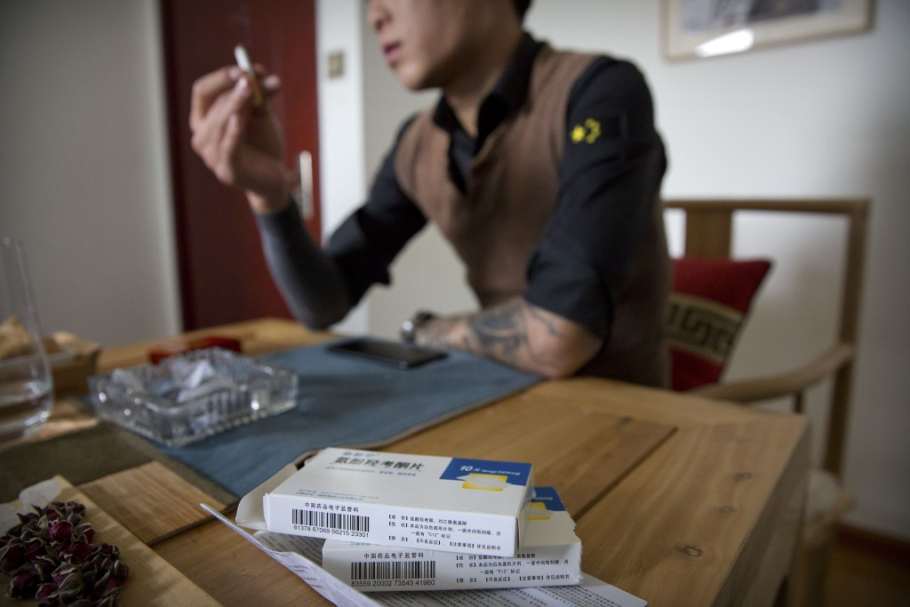 In this March 28, 2019, photo, Yin Hao, who also goes by Yin Qiang, talks about his addiction while sitting near boxes of Tylox pills he earlier purch...