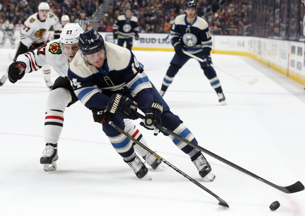 Columbus Blue Jackets forward Gustav Nyquist, right, of Sweden, controls the puck in front of Chicago Blackhawks defenseman Adam Boqvist, of Sweden, d...