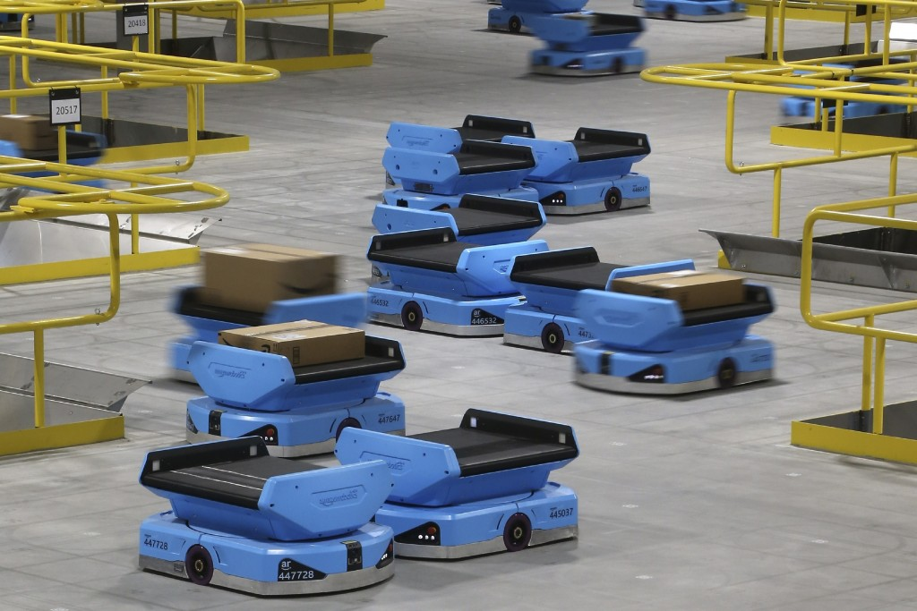 In this Dec. 17, 2019, photo Amazon robots zip along the a warehouse floor, transporting packages from workers to chutes that are organized by zip cod...