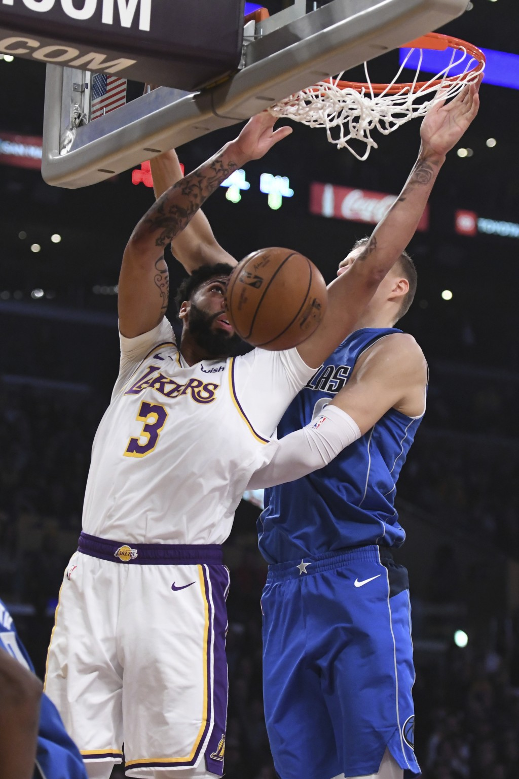 Los Angeles Lakers forward Anthony Davis (3) dunks against Dallas Mavericks forward Kristaps Porziņgis during the first half of an NBA basketball game...